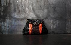 Luxury python and iguana leather handbag with a piece of  jewelry.