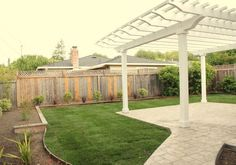 Backyard ideas: fence with lattice, beds around yard edges, covered stone portico