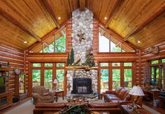 Looking into the Great Room from the Foyer.  Stone fireplace, patio doors with trapezoid windows, log walls, wood ceiling with log beams.