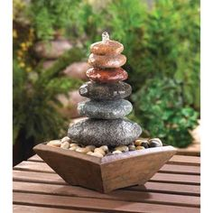 """Zen Stacked Stone Fountain (Item #15116)  The sound of water cascading over perfectly balanced stacked stones makes this a welcome meditation destination in your home. This fountain features multi-colored stones resting on a bed of pebbles, collected in a simple and lovely wood-liked base.  Item weight: 5.8 lbs. 8½"""" x 8½"""" x 11½"""" high. Polyresin. UL Recognized."""