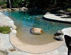 "Natural pool design by Expanding Horizons, based in Vista, CA. The approach is to construct ""hybrid pools,"" which incorporates technology commonly found in conventional pools, such as pool cleaners, sufrace skimmers, and main drains. Designs often include beach entries, and water plants are seeded into the nooks & crannies between the perimeter boulders to enhance the natural experience."