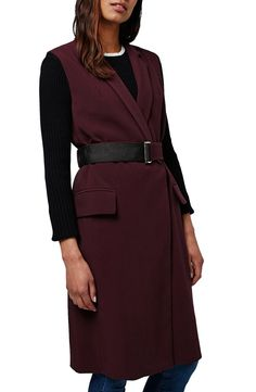 Transition to cooler weather in this sleeveless coat fashioned with a notched collar and flap pockets for a tailored feel. The versatile layer includes a matching D-ring belt trimmed in grosgrain for subtle contrast.