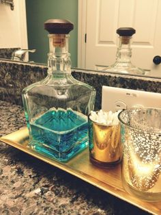 whiskey bottle recycled as a mouthwash holder- much prettier than plastic bottle... genius!