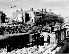 ISIGNY SUR MER 19 June 1944 – An American tank battalion passes through Isigny, France, with ruins of building damaged by shell fire and bombing in the background. (Photo : US Archives)