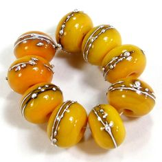 Opaque medium lemon yellow buttercup handmade lampwork glass beads. These gorgeous beads are made using opaque medium lemon yellow buttercup glass. This is a beautiful bright yellow orange glass. These look like beautiful jewels whether shiny or etched! They are beautiful beads that you can have in a shiny glass bead finish or go for the frosted handmade sea glass or beach glass look in an etched glass bead finish.
