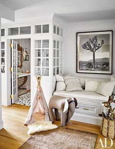 Nate Berkus - The nursery is clad in beautiful marble wallpaper lined with a gilded gold mirror and picture frames.