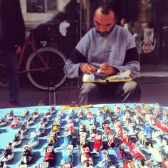 Vendor making soccer cleat keychains at San Telmo Sunday Market in Buenos Aires Argentina