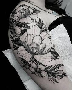 Tatuagem criada por Marquinho André de Porto Alegre. Pássaro com flores em preto e cinza no braço.