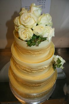 Four tiers of Coconut, Vanilla and lemon cake. Wrapped in pure withe chocolate and decorated with eatable gold! Fresh flowers arrangement.....