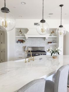 An angled marble island boasts length and class from Calcutta gold countertops paired with Restoration Hardware Hudson Camelback Fabric Stools under Regina Andrew Large Globe Pendants.