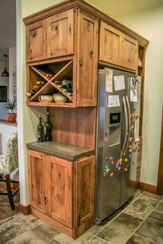 A wine rack and storage for bottles and bar supplies makes entertaining in this kitchen easy. Built around the refrigerator, this cabinet configuration creates a nook to hide the sides of the fridge. btbcabinets.com #winestorage, #barsupplies