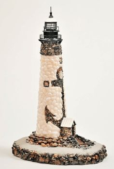 Anchor Lighthouse, inspired by St. Jude. The lighthouse is inlaid with seashells and sea stones hand picked by the artist. The sand is authentic Florida beach sand, and the anchor eye is inlaid with quartz-like stones from Cape May, NJ and also contains a tiny shell in its center.  seasideartistry.webs.com