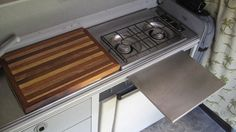 Great kitchen setup for camper. Custom cutting board fits over stove for traveling. Small stainless steel table fits in grooves for original Winebago tables. I like custom snap-in table idea; could be good for laptop table. maybe even adjustable height? Vw Eurovan Camper, Airstream Campers, Vw Camper, Beach Rides, Van Storage, Stainless Steel Table, Small Sink, Custom Cutting Boards, Cool Vans