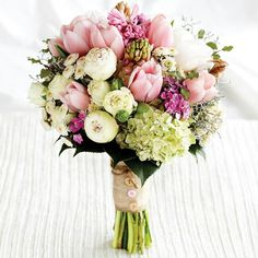 {Sweet & Romantic Bridal Bouquet Which Features: Pink Lilac, Pink Tulips, White Cabbage Rose, White/Yellow Button Mums, White Roses, White Peonies, Fuchsia Dianthus, Green Snowball Viburnum, Green Foliage, & Hand Tied With Cotton Ribbon With Buttons Added···············}