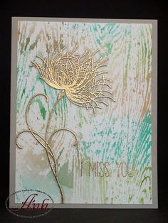 """By Anh. Stamp """"Dreamy"""" in VersaMark on vellum; heat emboss with gold powder. Hand cut with narrow border. Swipe Distress inks on craft sheet, spritz with water, tap woodgrain stamp into ink, then stamp on watercolor paper. Dry. Stamp sentiment in VersaMark; heat emboss with gold powder. Add flower."""
