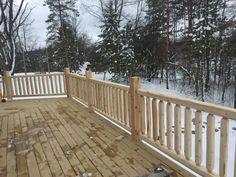 Classic white cedar log railing installed on this wraparound deck.