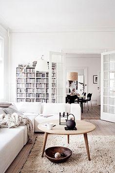 White couch, white shelves, white Moroccan Beni Ourain or flokati rug, wood coffee table