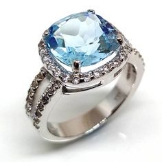 The beautiful blue of a summer sky sparkles in this split shank square shaped cushion cut blue topaz engagement ring with diamond simulant halo from Luxuria Hexagon Engagement Ring, Gemstone Engagement Rings, Halo Diamond Engagement Ring, Diamond Wedding Rings, Gemstone Rings, Blue Topaz Diamond, Topaz Gemstone, Diamond Simulant, Prong Set