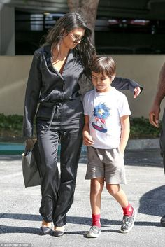 Doting mom: The reality star wore a black silk jumpsuit while her eldest son was dressed i...