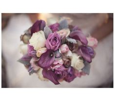 Incorporate purple into a winter wedding by selecting a bouquet crafted with soft-hued plum flowers, white buds, and dusty miller.