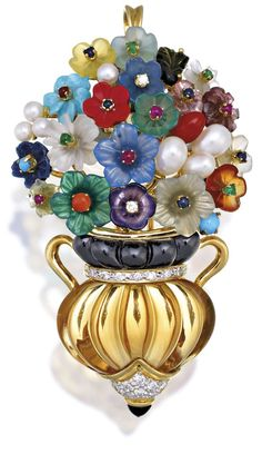 DIAMOND AND GEM SET PENDANT/BROOCH Of giardinetto design, the bulbous vase decorated with fluted citrine, onyx and circular-cut diamonds, the floral arrangement highlighted with pearls and multi-coloured carved gemstones, mounted in 18ct gold, length approximately 60mm.