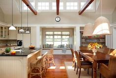 Who wouldn't have fun cooking and entertaining in this kitchen space? Look at the amazing open ceiling and the light pouring in from the line of windows. Miles of countertop and a place for everyone to perch. What a dream!