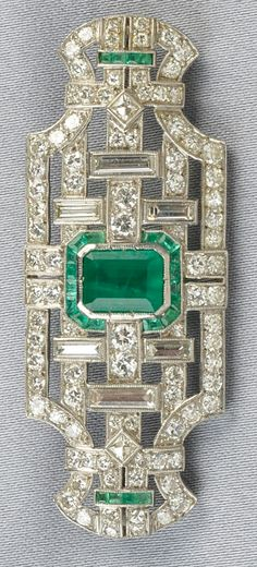 Art Deco Platinum, Emerald, and Diamond Brooch, set with an emerald-cut emerald measuring approx. 8.20 x 6.10 x 4.30 mm, further set with baguette-, old European-, single-, and fancy-cut diamonds, approx. total diamond wt. 3.00 cts., fancy-cut emerald accents, millegrain details, lg. 2 1/8 in. #Diamondbrooch