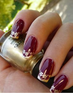 Dark red nails with gold flowers