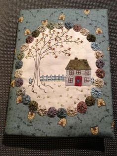 A pretty journal cover by Lynette Anderson. Love the yoyo frame and house and treeA pretty journal cover by Lynette Anderson. Love the yoyo frame and house and tree Fabric Art, Fabric Crafts, Sewing Crafts, Quilting Projects, Sewing Projects, Fabric Book Covers, Fabric Journals, House Quilts, Penny Rugs