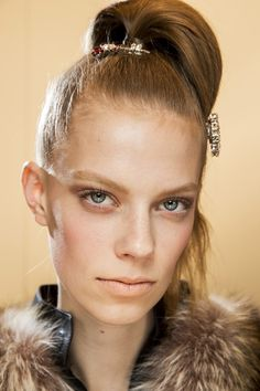 Fall 2015 beauty - Guido Palau at Prada  styled the hair in sleek high ponytails fastened at the top of the head.
