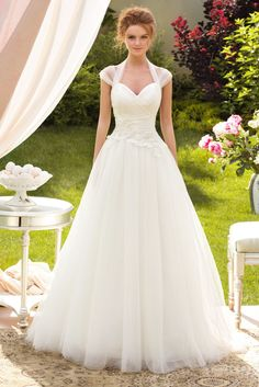 "A delicate and light dress. The abundance of tulle and clever drapery create softness and volume. The thick bodice with lace up corset and a romantic cut ""heart"" neckline emphasize the brides femininity. The transparent tulle shoulder straps cover the shoulders delicately and the handmade beaded roses on the bodice as just a tad of […]"