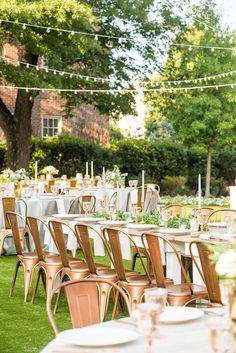 Mikkel Paige Photography pictures from a wedding at Merrimon-Wynne House in Raleigh, NC. Photo of the outdoor reception on the lawn, with round and farm tables, pink linen napkins, grey plates, and floral centerpieces.