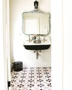 A peek into one of the guest room bathrooms. vintage industrial style sink and art deco mirror