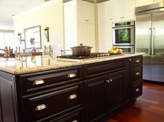 Island with dark wood cabinetry with modern drawer handles, contrasting the surrounding white kitchen cabinets. #homestyle #homedecor #kitchenisland #kitchenremodel