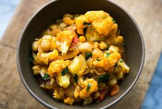 Delicious vegan curry with cauliflower, chickpeas, onion, tomato, and cilantro. So EASY! #healthy On SimplyRecipes.com