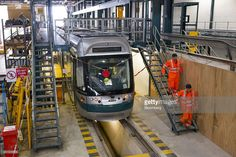 Alstom SA employees descend stairs before working on an Incentro tram, manufactured by Bombardier Inc