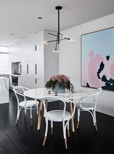Dining - gloss white marble round dining table with wooden legs, white Thonet bentwood armchairs with timber legs, black branch lights, blue and pink pastel painting artwork, panelled light grey kitchen cabinet doors, dark floorboards