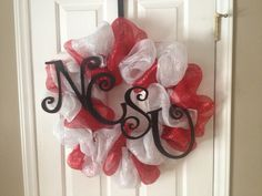 Use a wire wreath and tie mesh loosing around the ring.  Spray paint wooden letters.  After drying, hot glue the letters together and attach to the wreath with fishing line.