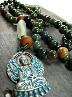 Spiritual Grounding Mala - ​10mm Moss Agate beads with two bodhi seeds and a unakite bead, adorned with a recycled African glass guru bead and a buddha pendant.  Moss Agate has an excellent quality that helps you to correct imbalances between the left and right sides of the brain and it may stimulate your spiritual grounding capabilities. This aids you to move forward with your life using a more united and balanced thought process. $40 http://www.malaforvets.org/shop/spiritual-grounding-mala
