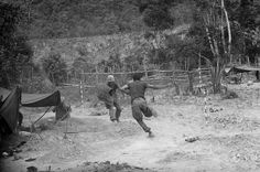 """U.S. Marines run to their foxholes as North Vietnamese mortars begin zeroing in on their positions during Operation Hastings near the demilitarized zone between North and South Vietnam on July 17, 1966. (AP Photo/Horst Faas)"""