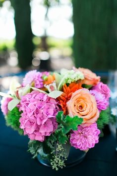 Colorful floral centerpiece with neon pink hydrangea, dahlias, peach roses and vivid greenery. Mandy Scott Flowers.
