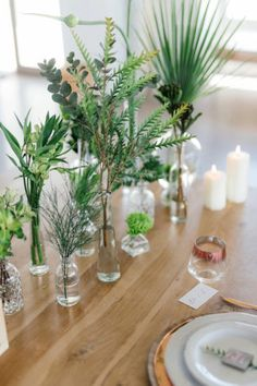 Greenery and Copper Wedding tablescape using mixed glass bottles of varying heights and textures, with single stem green flower arrangements. Minimalist and chic botanicals!