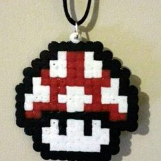 Gaming styled Mario necklace in the shape of the magic mushroom from the Mario video games. Made from white, black and red hama beads this Mario necklace is sure to make you stand out in the crowd. Complete with a removable 30″ cord necklace that can can be shortened to any desired length or removed to be replaced by a silver necklace (Not supplied) or to be used as a decoration.
