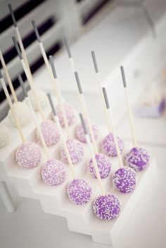 Purple ombre vanilla and chocolate cake pops with white sprinkles  Ends of sticks dipped in edible silver paint.  Cake pop stand available for hire. Photo by Rosie and Rolf Photography.