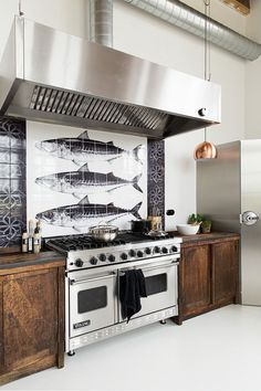 Professional navy & wood kitchen with stainless steel appliances, tiled back splash