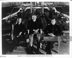 Actors Barbara Bach and Roger Moore sitting in front of a submarine tank at Pinewood Studios with producer Albert R. Broccoli between them, during the making of the James Bond film 'The Spy Who Loved Me', 1977.