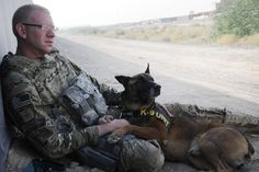 U.S. Air Force Staff Sgt. Chris Fall, a Military Working Dog handler, relaxes with his dog, Glenn, a Patrol Explosive Detection dog, before an early-morning training exercise at Kandahar Airfield, Afghanistan, July 9, 2012. The handlers and their dogs rotate through Kandahar Airfield for validation prior to moving out to forward operating bases around the country where they will lead combat foot patrols and sniff out IEDs and other explosives.