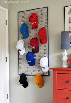 Virtue of necessity: baseball caps hang from pegboard.