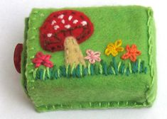 Sweet Little Felt Box. No tutorial, just this photo. Seems easy to make: just decorate, sew edges together over a cardboard form. (You could leave the box in for stability, or remove it.)