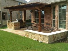This outdoor patio in Southlake, Texas features a flagstone patio surface with outdoor barbecue grill nook and custom stone surround walls for additional seating. www.landscapedesignmidcities.com